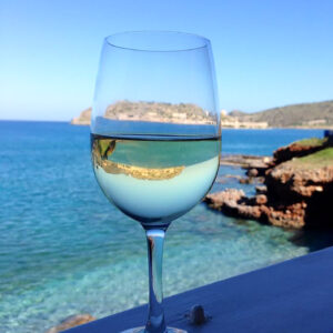 Greek Wine: a glass of white wine at the ocean