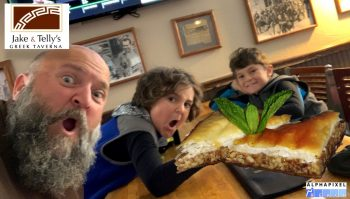 Jake and Telly's Kids' Menu: A photograph of Jake and his two sons at a table looking very excited about a piece of Baklava.