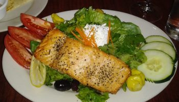 Photo of a Greek Salad with grilled Scottish Salmon on a white plate.