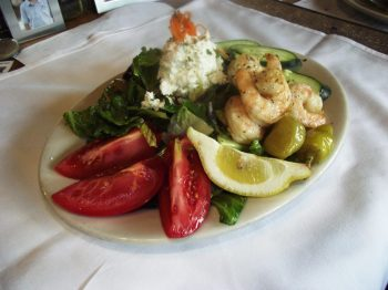 Photo of a Single Serving of Greek Salad with shrimp on a white plate: Hand cut romaine lettuce, fresh tomato, cucumber, red onion, marinated olives, pepperoncini peppers, feta cheese topped with our house-made herbed vinaigrette dressing.