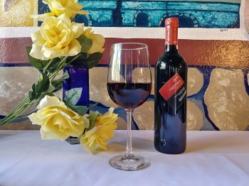Nemea Red Wine from Greece: A photo of a bottle and glass of Nemea Red wine on a white tablecloth with yellow roses to their left. The wine glass is in the center, the bottle on the right. The collage is in front of a frescoed wall depicting a rock wall and a windowsill.
