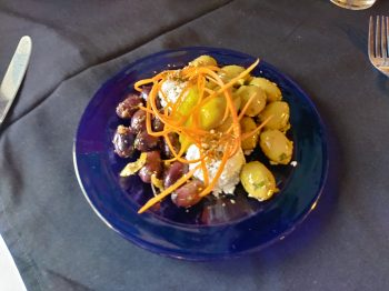 Appetizer: Photo of Marinated Olives & Feta Cheese Plate. Imported Greek black and green olives on a blue plate with Feta cheese and garnished with julienned carrots.