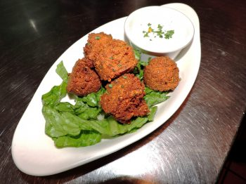 Appetizers: Photo of Jake and Telly's hummus balls in a white oval dish on a bed of lettuce and with a side of tzatziki sauce.