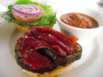Vegetarian Sandwiches at Jake and Telly's: eggplant Burger with soup. A close up photo of our Eggplant Burger. Grilled eggplant on a toasted brioche bun with, roasted red pepper, feta cheese spread, lettuce, fresh tomato, and red onion. Your choice of sides: roasted potatoes, coleslaw, garlic mashed potatoes or a cup of soup.