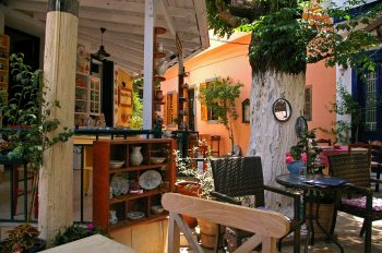Jake and Telly's Catering: A photo of a covered, open-air patio on the Island of Samos. The patio is shaded by an open air roof and a large tree. Two tables are visible, along with three chairs, pottery on shelves and live potted trees and flowers. An orange wall is visible in the background.