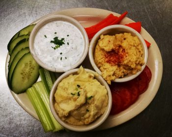 Appetizers: The Greek Dips. a Photo of our Hummus, Tzatziki and Skordalia on a white plate with fresh tomatoes, celery, carrots, and sliced cucumber.