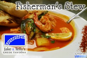 Entrees at Jake and Telly's: Fisherman's Stew (Psaras Stifado). close up photo of fisherman's stew. a red tomato sauce in a white bowl with Lemon wedge and grilled garlic bread