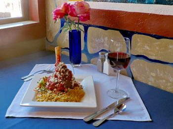 Entrees at Jake and Telly's: Lamb Shank (Arní Giouvétsi). A close up photo of our Colorado lamb shank, braised in our house-made Greek tomato sauce. Served with herbed orzo, Feta cheese, and sautéed vegetables.