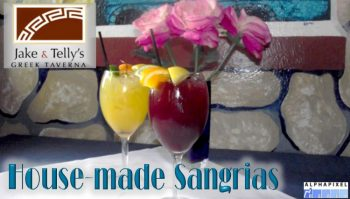 "House Made Sangrias: Photo of red and white sangrias in front of pink roses on a blue plate. They are in front of a frescoed wall depicting rocks. A red Jake and Telly's logo is in the upper left, the text ""House made Sangrias"" is in the lower left, and the Alphapixel Reach logo is in the lower right corner."