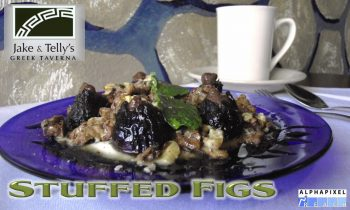 "Dessert at Jake and Telly's, Stuffed Figs: A photograph of a blue plate of Stuffed Figs on a white tablecloth with a cup of coffee and a fork and spoon visible behind them. The figs are stuffed with cinnamon, vanilla, and crushed walnuts then topped with Greek yogurt and honey. A Green Jake and Telly's logo is in the upper left hand corner and the text ""Stuffed Figs"" is present beneath the plate. The AlphaPixel Reach logo is in the lower right hand corner."