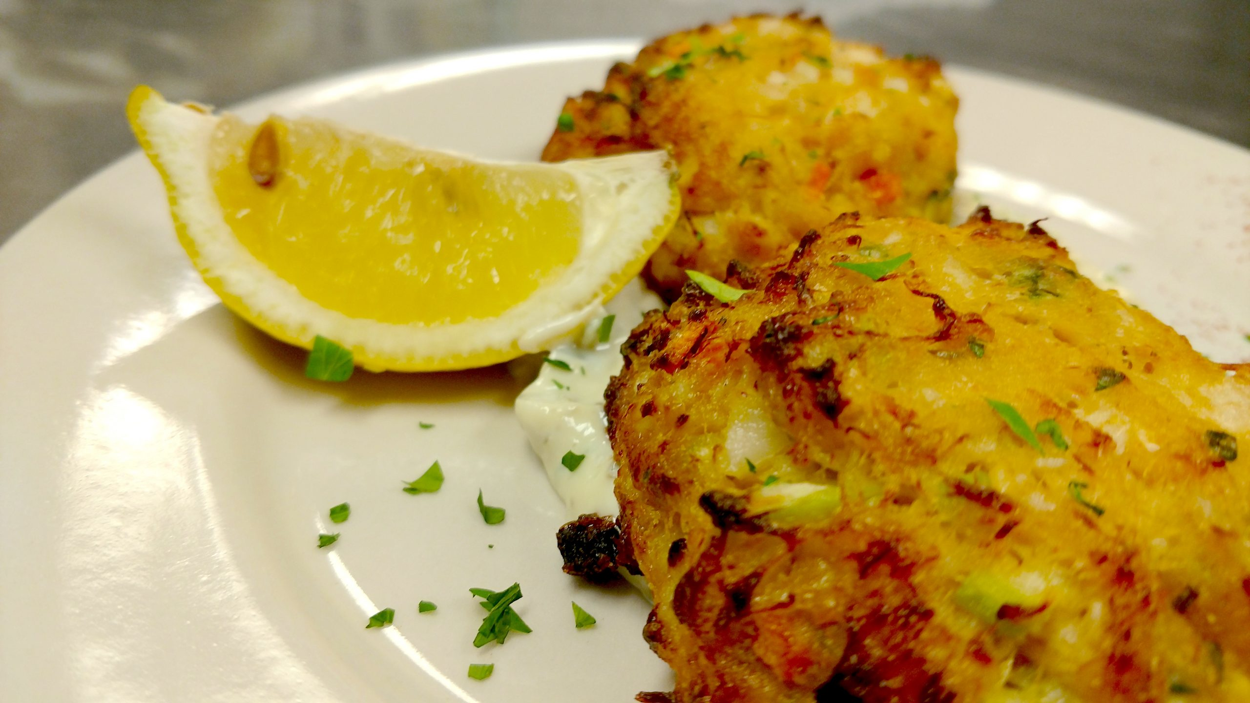 Jake and Telly's Specials - Crab Cakes. A Close up image of crab cakes on a white plate with a lemon wedge