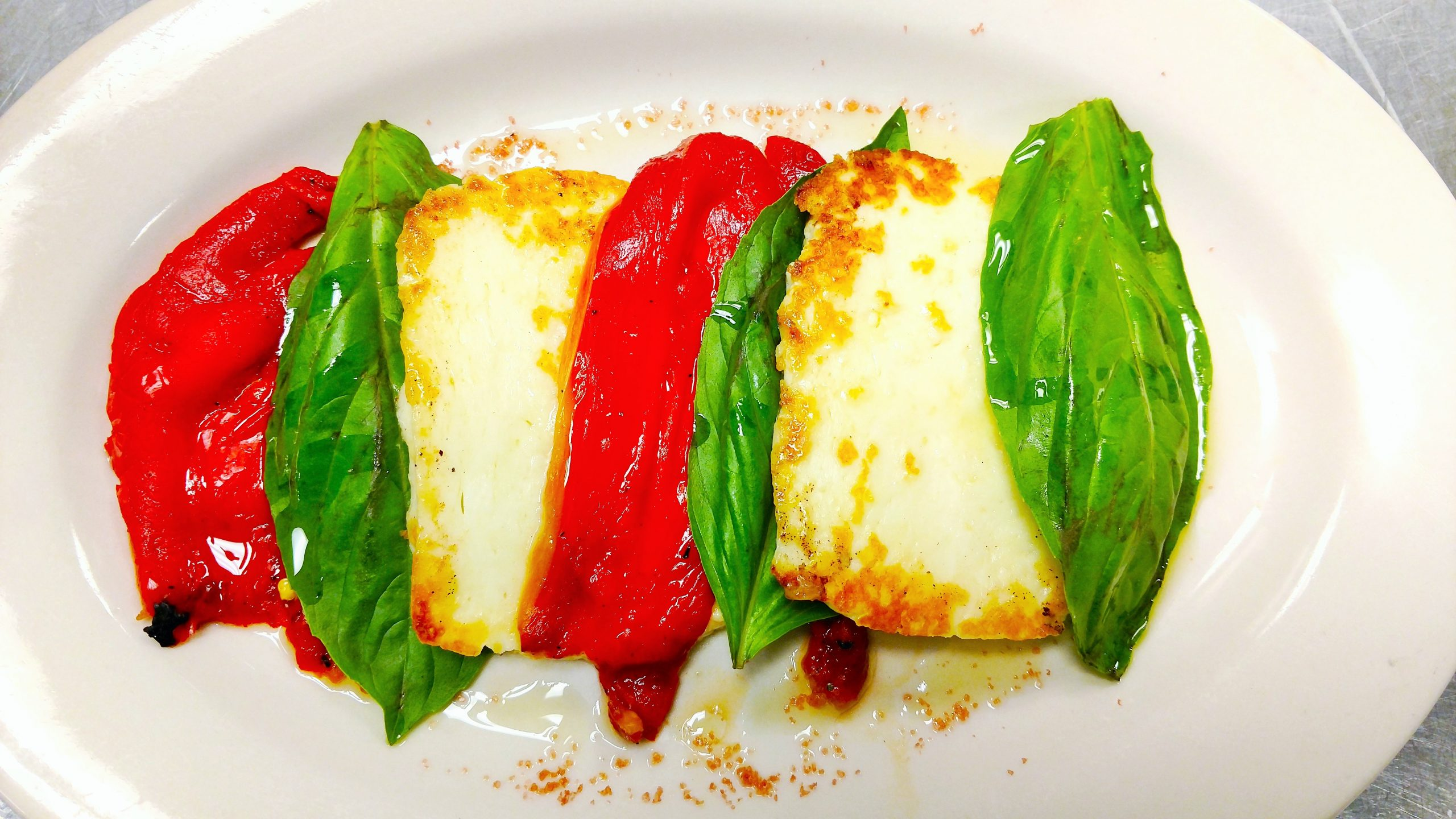 Jake and Telly's Specials - Close up of the haloumi & Peppers. Red peppers, green basil leaves, and white haloumi cheese on a white plate.