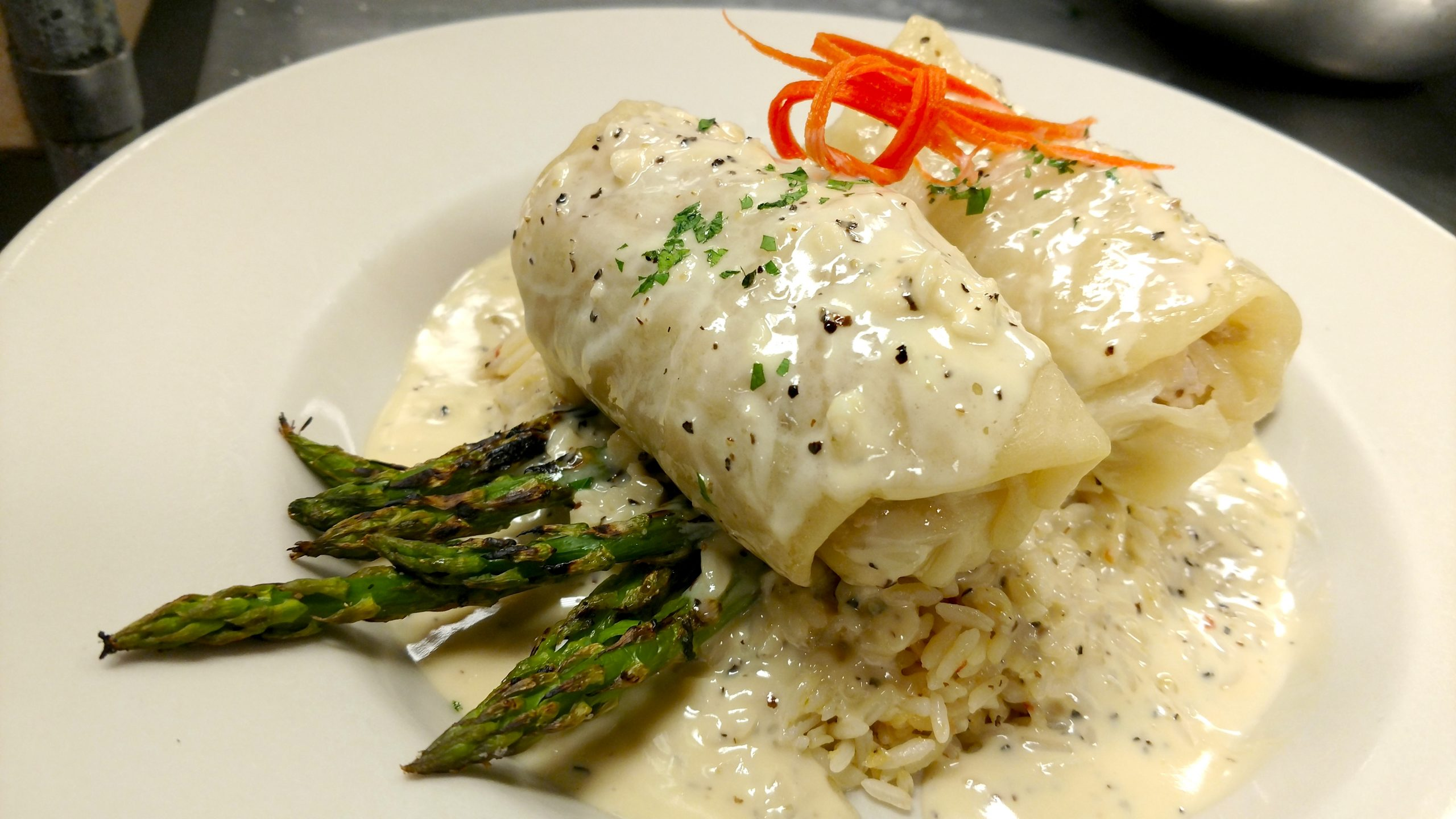 Jake and Telly's Specials - A close-up image of stuffed cabbage on top of asparagus and rice smothered with a white sauce and garnished with carrot and green parsley.