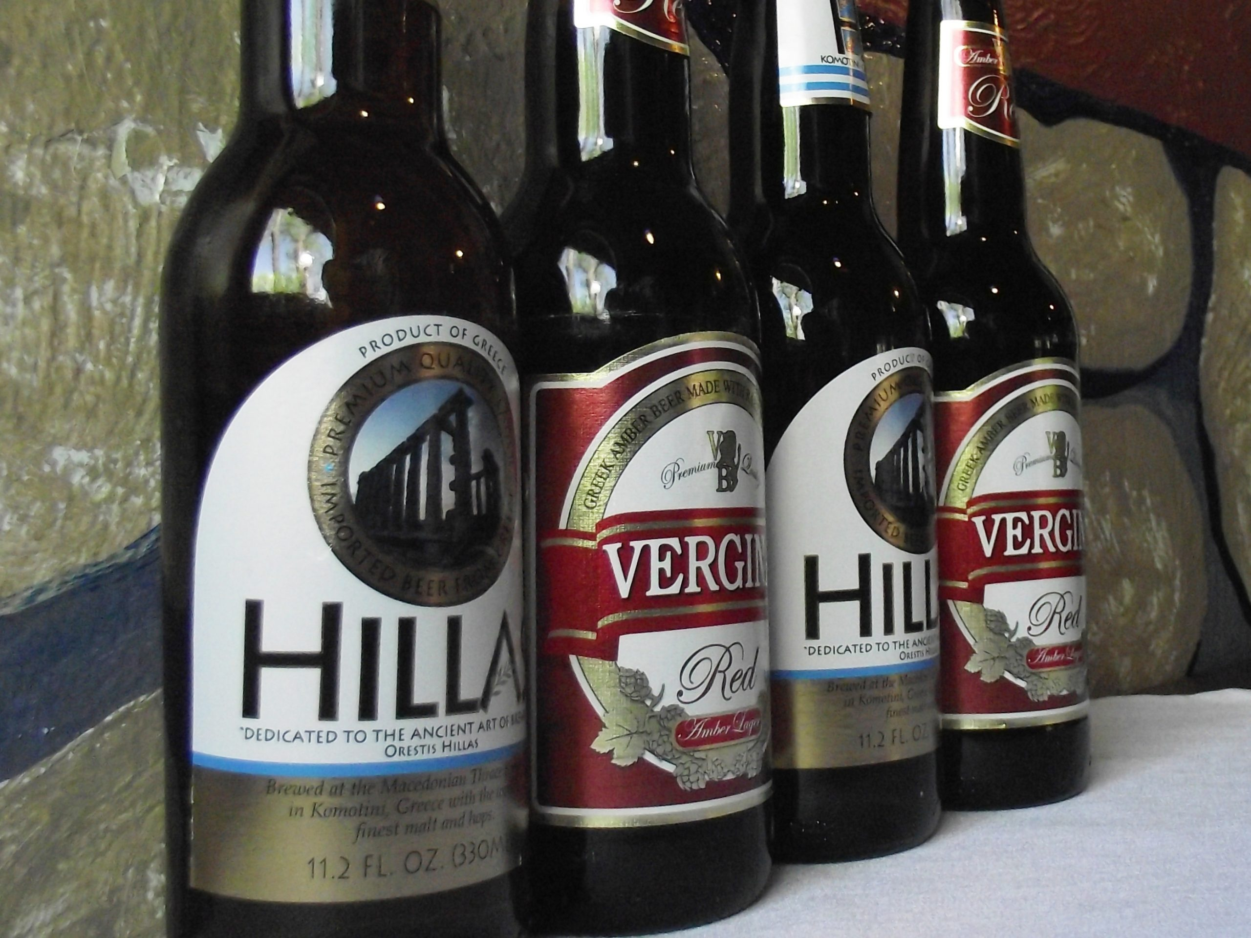 Four bottles of Greek Beer, Hillas Lager and Vergina Red Ale, on e teble with a white table cloth and with frescoed rocks as a background
