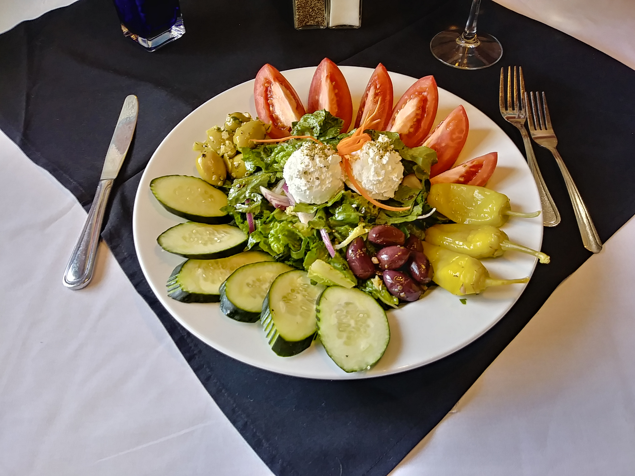 Photo of Jake and Telly's Family Sized Greek Salad on a white plate: Hand cut romaine lettuce, fresh tomato, cucumber, red onion, marinated olives, pepperoncini peppers, feta cheese topped with our house-made herbed vinaigrette dressing.