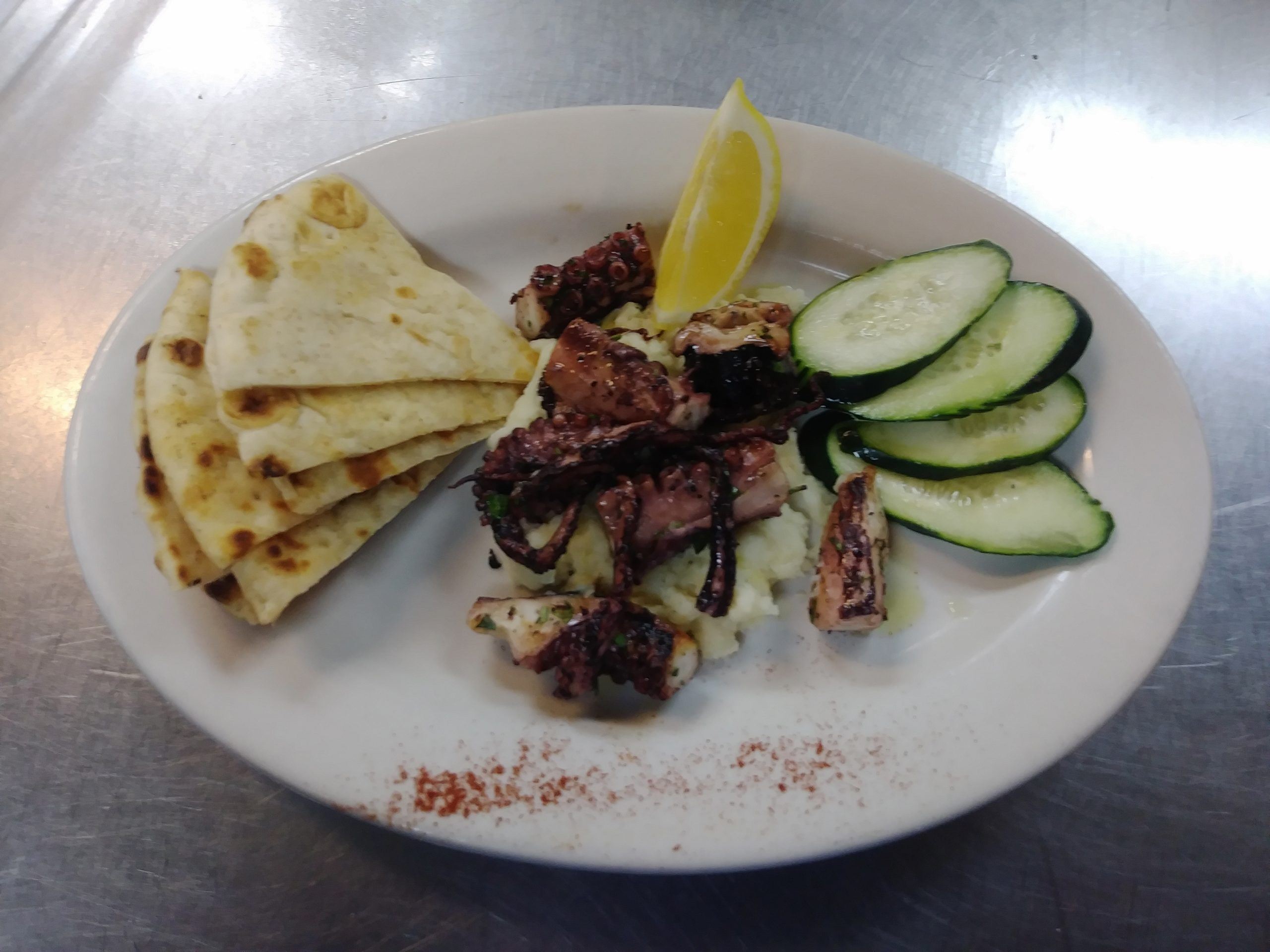 Appetizer: Jake and Telly's Grilled octopus on a white plate. Octopus marinated in our secret blend of herbs and spices, then char-grilled to perfection. Served with a classic Greek Skordalia (garlic and potato dipping sauce), cucumber, lemon and warm pita.