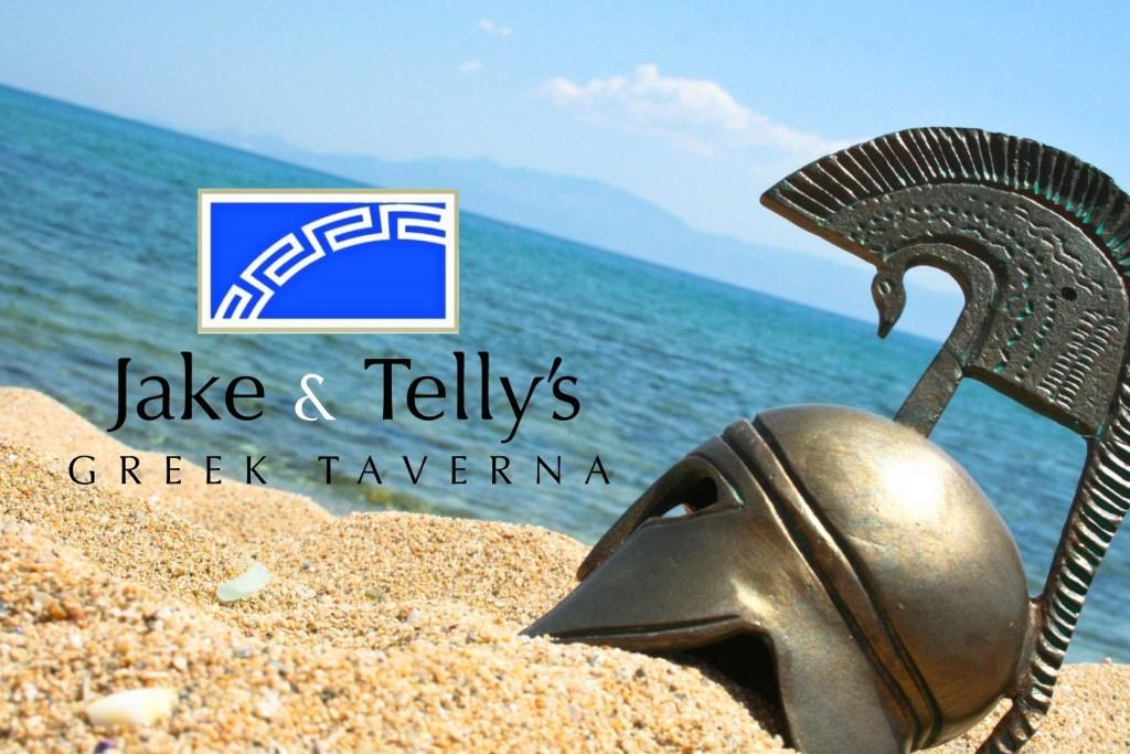 Jake & Telly's Greek Taverna: A photo of a homeric helmet in the sand on a beach with the blue ocean and blue sky visible in the background. The helmet is on teh right side of the photo and photo's horizon is at approximately a 25 degree angle and a Blue Jake and Telly's logo is present to the left of the helmet.