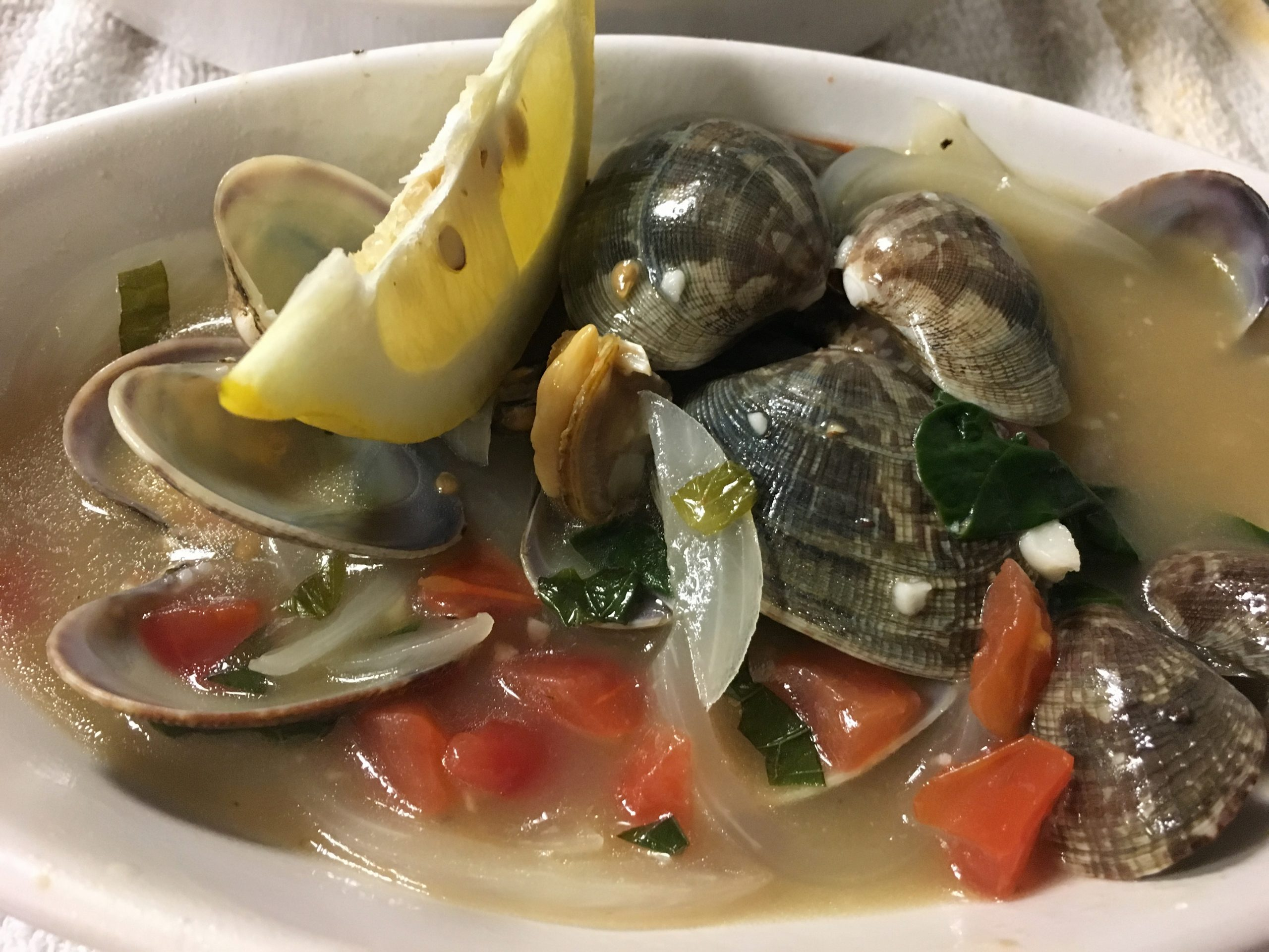 Appetizer: photo of Little Neck Clams in a white bowl. Little neck clams sautéed in garlic butter, white wine and fish fumé. Served with grilled bread.