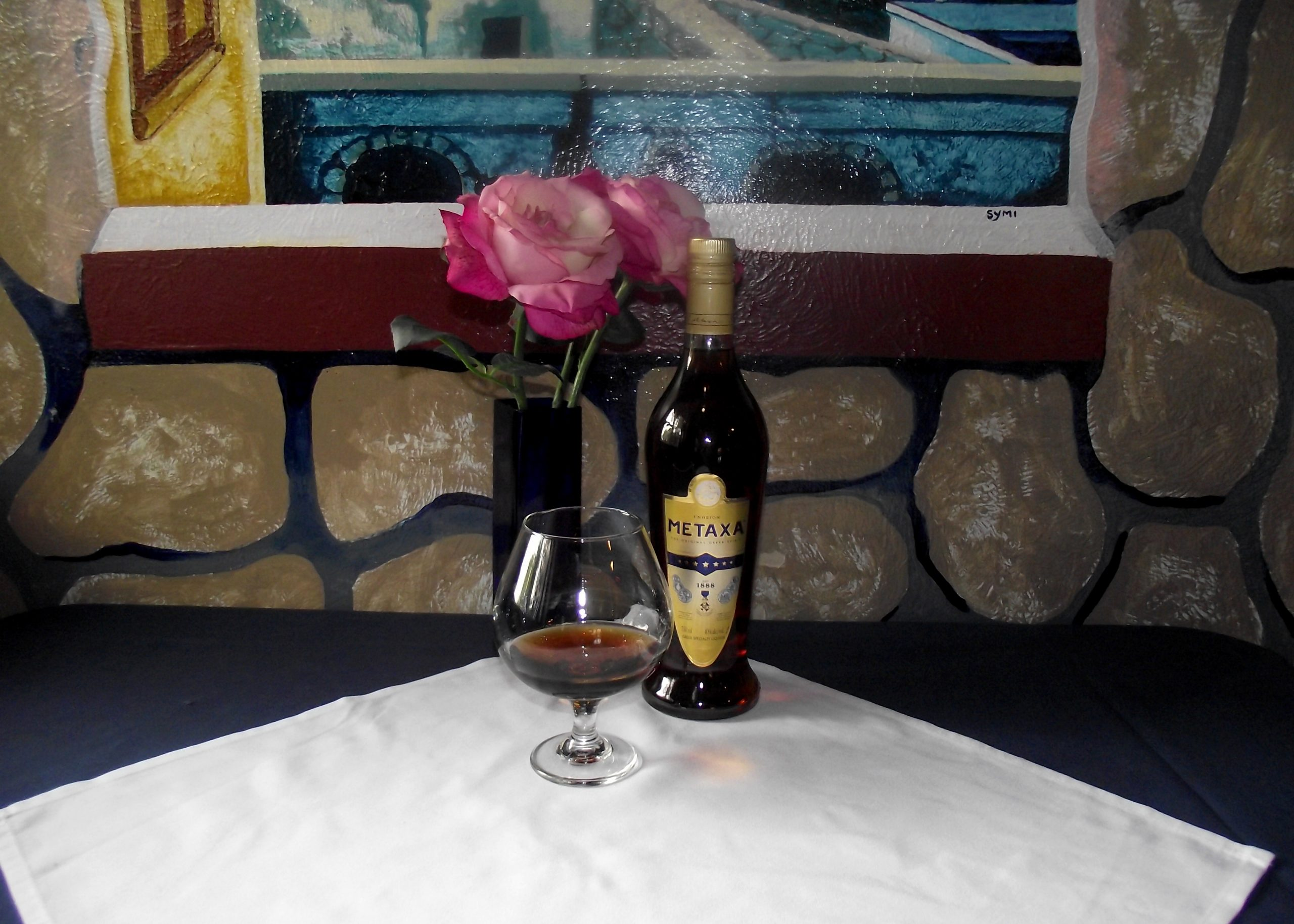Metaxa: A photo of a brandy snifter with brown liquid setting on a white square tablecloth. A blue vase with pink roses is behind the brandy snifter to the left and a bottle of seven-star Metaxa is behind the brandy snifter to the right. the collage is in front of a frescoed wall depicting a rock wall and a windowsill.