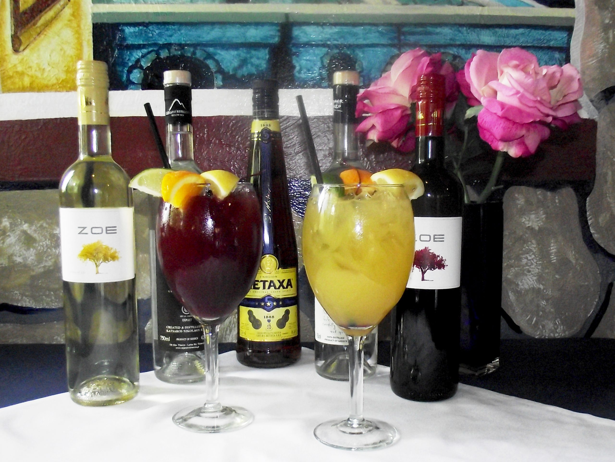 Two glasses of Sangria with bottles of red and white Zoe and Metaxa spirits